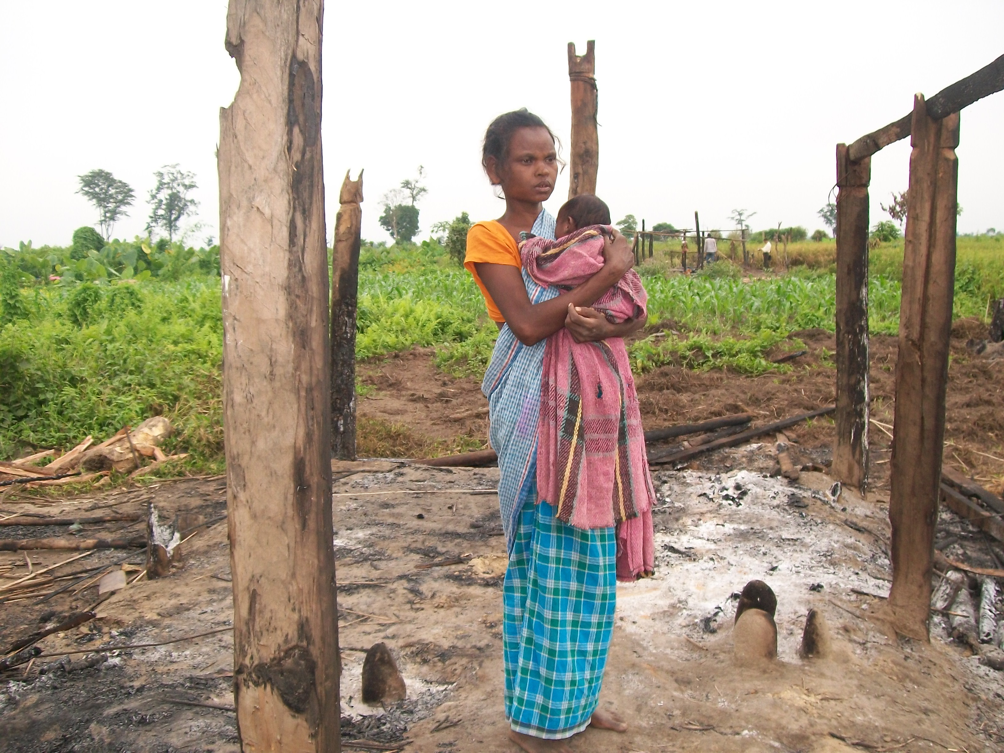adivasi-woman-with-her-kid-in-burnt-house.JPG