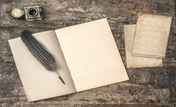 Open book, vintage writing tools feather pen and inkwell